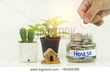 hand put money coins in bottle and home concept in house finance