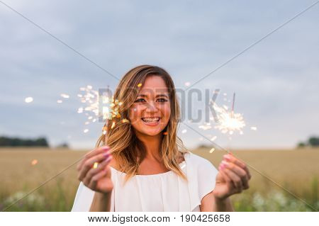 Young pretty woman having fun with a sparkler outdoors.