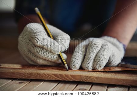 Close-up of craftsman hands in gloves measuring wooden plank with ruler and pencil on workbench. Concept of woodwork and handcraft.