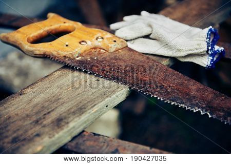 Close-up of rusty old manual saw and protective gloves on wooden plank. Concept of craftsmanship and woodwork.