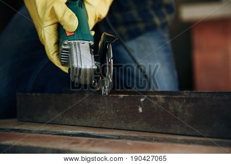 Male constructor hands cutting metal with grinding machine.