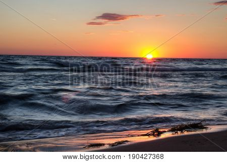 Sunset Beach Background. Sunset sky and waves crashing on the beach along the Lake Michigan coast.