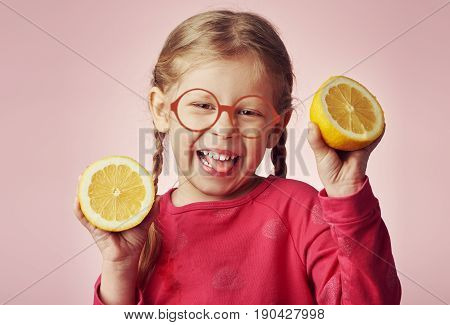 Funny picture of pretty girl with pigtails showing halves of lemons and grimacing.
