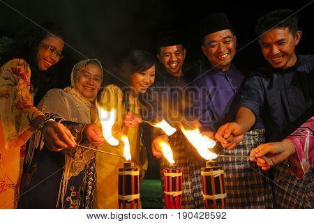 MALACCA MALAYSIA - SEPTEMBER 10 2008 : Men and woman light up the Malay tradition oil lamp or pelita during Hari Raya celebration.