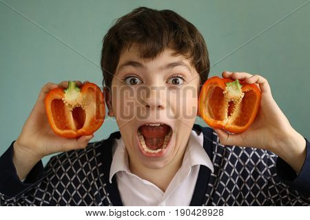 teenager boy with cut paprica red sweet pepper ears close up creative portrait