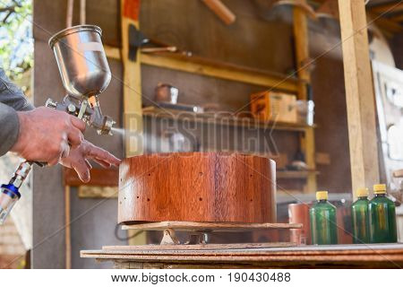 Carpenter spraying lacquer on merbau wood drum shell at workshop