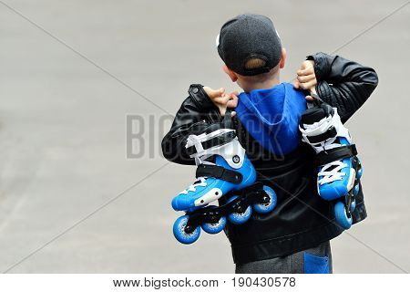 little beautiful boy with roller skates in his hands. Street culture backgroung, rollerblading