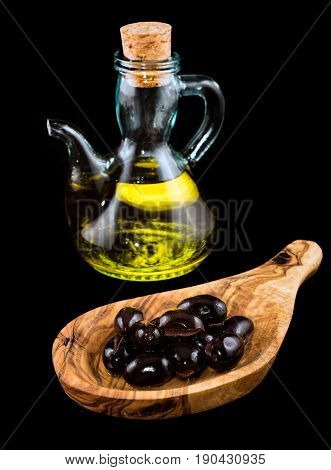 Black olives in wooden spoon and bottle of olive oil on black background