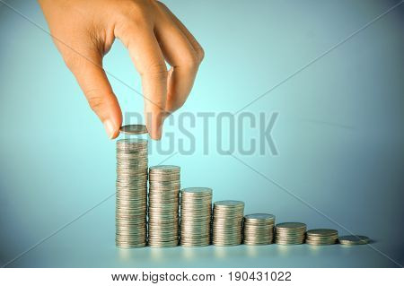 hand pum money on pile of coins on blue background concept in save and grow up