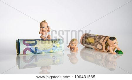 Small baby toys and euro money with white background children figures with euro bank notes