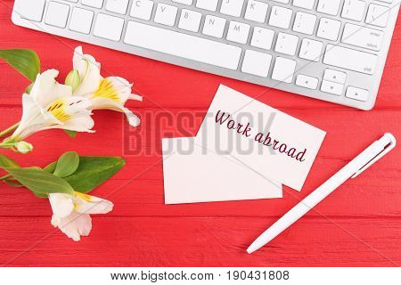 Keyboard and business card with text WORK ABROAD on red wooden background. Recruitment concept