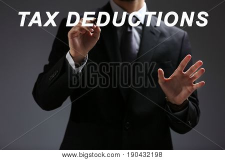 Man pointing on text TAX DEDUCTIONS against gray background