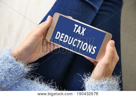 Tax deductions concept. Woman with smartphone, closeup