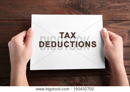 Woman holding paper with text TAX DEDUCTIONS on wooden background