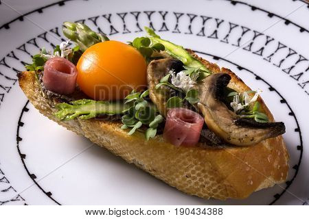 Bruschetta With Fried Mushrooms And Egg Yolk On A Plate