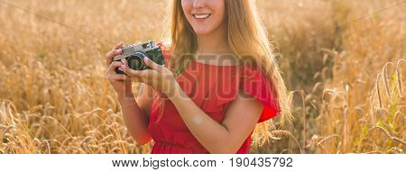 Portrait of beautiful young smiling woman with camera in the field.