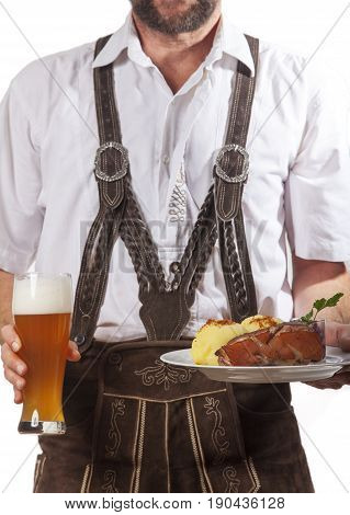 bavarian man in leather trousers with roasted pork