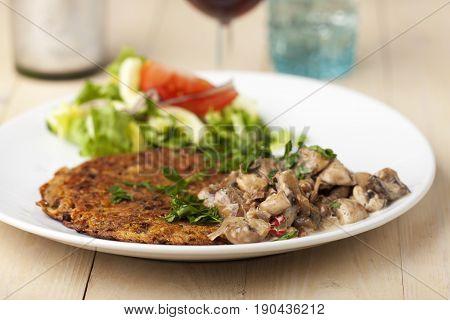 potatoe pancakes with mushroom sauce on wood
