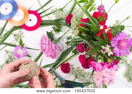 Man with his hands to make a beautiful flower arrangement the concept of flower design ikebana. view from above
