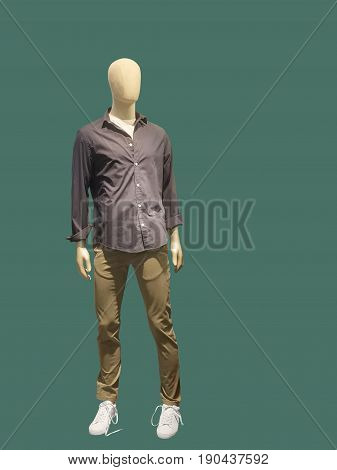 Full-length man mannequin dressed in casual clothes isolated on green background. No brand names or copyright objects.