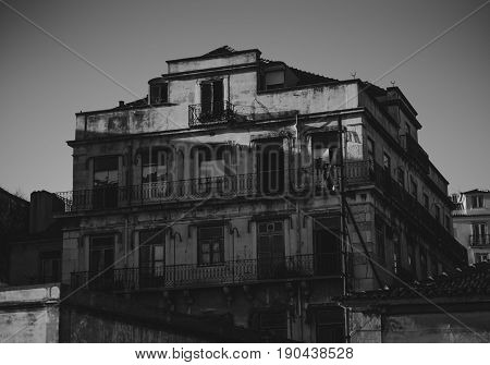 Black and white shooting of big four-story stone abandoned house in Lisbon with long balconies empty apartments and broken windows on bright day with clear sky Portugal