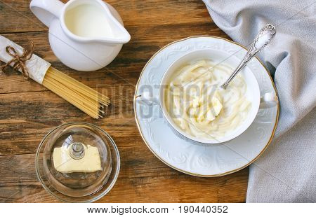 sweet dairy noodles in white bowl on plate towel oiler spaghetti on wooden table