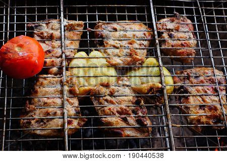 Pork meat with vegetables is fried on a grate
