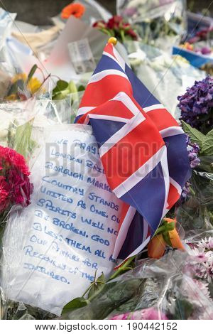 London, UK - 7 June 2017: Floral tributes and a Union Jack laid as a memorial to the victims of the terrorist attack that to place in Borough Market and London Bridge on 4th June 2017.
