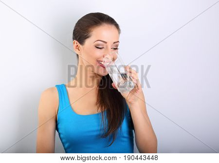 Young Beautiful Woman Drinking Fresh Pure Water From Glass On Blue Background With Happy Smiling