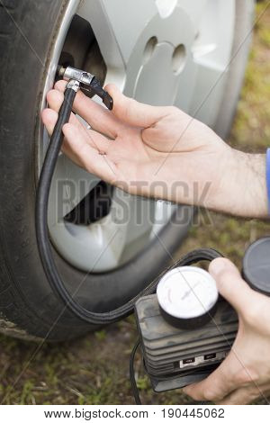 Insert the tip into the valve and pump the car wheel with a portable compressor at 12V