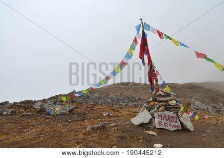 Mardi Himal Base Camp in Nepal, Annapurna region. Prayer flags in fog.