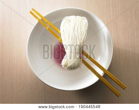 A pair of red chopsticks on a white bowl with noodle on top of it
