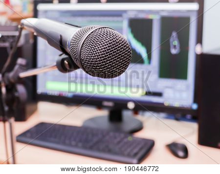 Microphone on the background of the computer monitor. Home recording Studio. Close-up. The focus in the foreground. Blurred background. Software for recording and editing sounds. Postproduction