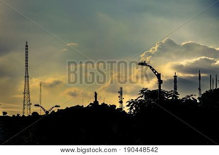 High contrast urban scene with anthenas silhouette and trees against cloudy sky background