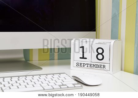 Cube shape calendar for SEPTEMBER 18 and computer keyboard on table.