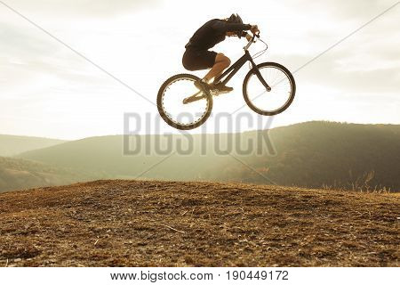 Side view of man in sportswear jumping high on mountain bicycle on background of landscape.