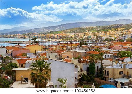 View of resort Greek architecture Rethymno city-port built by Venetians from height of Fortezza Castle - fortress on hill Paleokastro. Red tiled roofs and mountains in background. Crete Greece