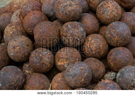 Texture of old cannonballs in courtyard of Fortezza Castle - Venetian fortress with Bastion defense system on hill Paleokastro in resort Rethymno. Greek historical attractions. Crete Greece