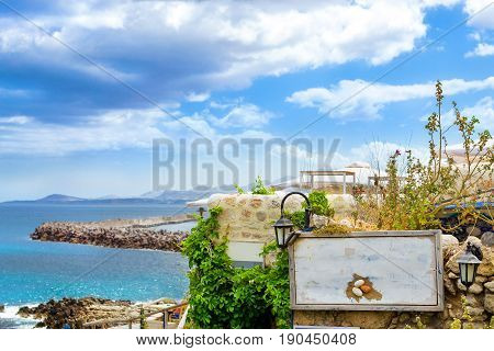 White signboard on stone wall of outdoor resort cafe on top of hill above highway along promenade Emmanouil Kefalogianni. Greek architecture on coast of Kolpos Almirou. Rethymno Crete Greece