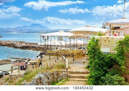 Outdoor resort cafe with white parasols on top of hill above highway along promenade Emmanouil Kefalogianni. Greek architecture on coast of Kolpos Almirou. Rethymno Greece poster
