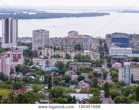 The city's skyline. The Russian province of Saratov. High-rise residential buildings, the Volga river and the railway bridge on the horizon