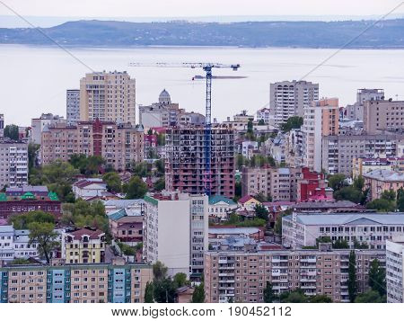 View of the city of Saratov from the mountain. The urban landscape, infrastructure, tenement houses, public buildings and streets, the Volga river on the horizon. Russian province.