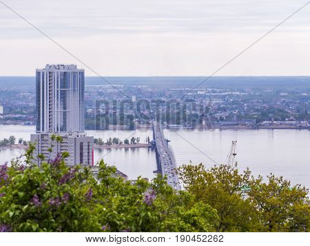 Road bridge between the cities of Saratov and Engels. Urban landscape, architecture. Multi-storey building. Blooming lilac bushes in the foreground.