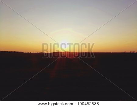 The photo is taken in the field on an open and flat terrain. The photo shows a horizon line well.