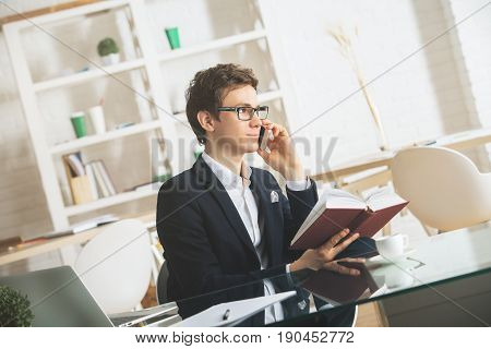 Side portrait of handsome young businessman with open book using smartphone at workplace. Distraction concept