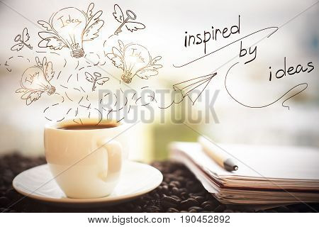 Close up of coffee cup notepad with pen and creative sketch on blurry city background. Inspiration concept