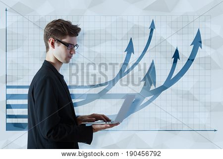 Thoughtful young businessman using laptop on polygonal background with upward chart arrows. Financial growth concept