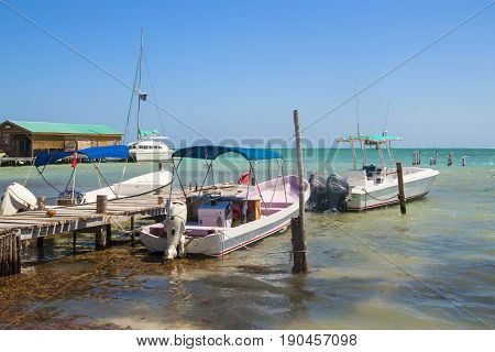 Beautiful tropical shore with pier for boats on the island of Caye Caulker on the Barrier Reef in the Caribbean Sea