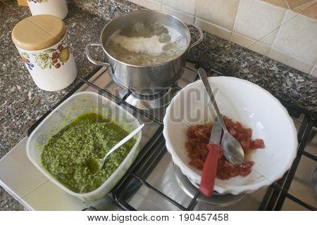 cooking pasta basil pesto sauce and fresh tomatoes