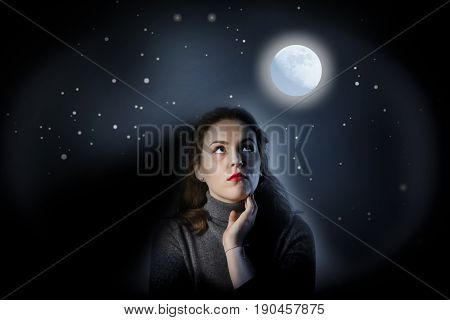 Girl in grey is looking at full moon. Girl full of doubts and hesitation
